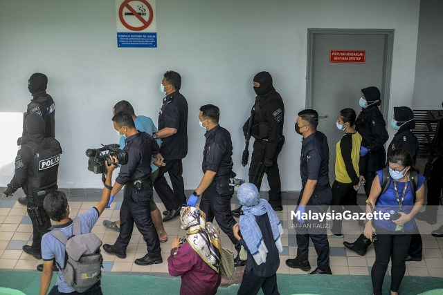 The two accused, Mohd. Fadzli Abdull Razak and Zuraida Atan are escorted by the police from the Melaka Criminal Investigation Department (CID) to the court to face murder and abuse charges of Zubaidi Amir Qusyairi Abd. Malek at the Melaka Courts Complex in Ayer Keroh.     PIX: AFFAN FAUZI / MalaysiaGazette / 10 FEBRUARY 2021