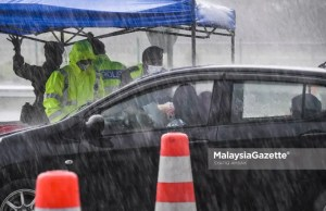 The police and Malaysian Armed Forces (MAF) inspecting the interstate travel permit in the rain at the Gombak Toll Plaza following the nationwide Movement Control Order (MCO) and interstate travel ban to curb the spread of Covid-19. PIX: SYAFIQ AMBAK / MalaysiaGazette / 16 MAY 2021.