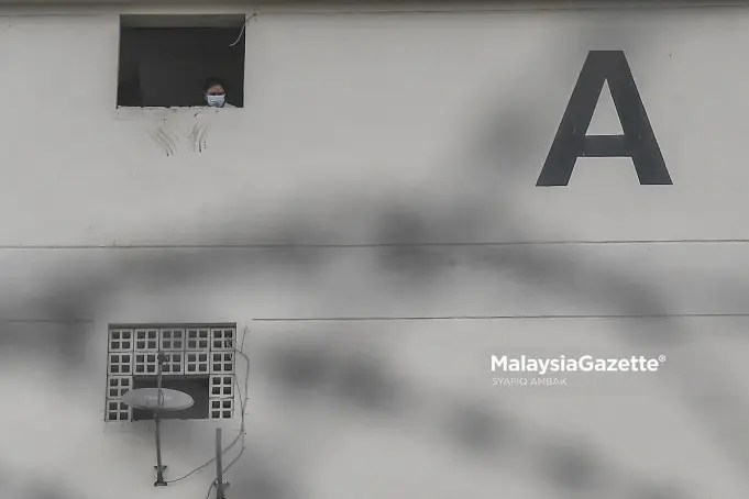 (Picture for representational purposes only). A resident of the Desa Rejang Flat in Kuala Lumpur looking out of a window after the Enhanced Movement Control Order (EMCO) is implemented on the flat. PIX: SYAFIQ AMBAK / MalaysiaGazette / 23 JUNE 2021