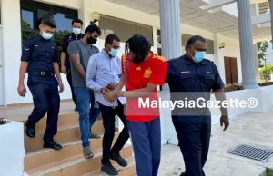 Police escort Datuk Seri (centre), his son (front) and a staff from his company to the Balik Pulau Court in Penang over RM304 million of Criminal Breach of Trust (CBT). NAR Trading investment scam
