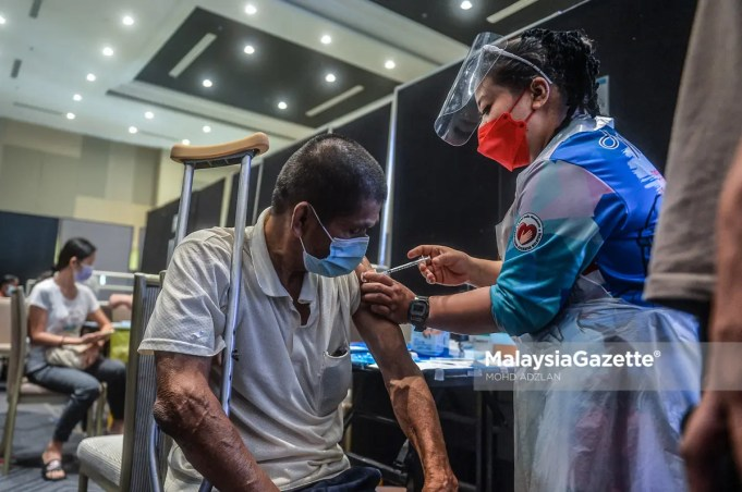 Healthcare worker administering Covid-19 vaccine on a person with disability at the UCSI University, Cheras vaccination centre. PIX: MOHD ADZLAN / Malaysiagazette / 07 JULY 2021. doses vaccination