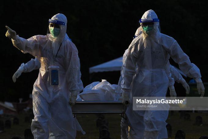 Healthcare workers managing Covid-19 bodies at the Bukit Kiara Muslim Cemetery in Kuala Lumpur. PIX: SYAFIQ AMBAK / MalaysiaGazette / 27 JULY 2021. Covid-19 death fully vaccinated Covid-19 deaths