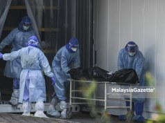 The staff managing Covid-19 bodies for burial at the One-Stop Corpse Management Centre (PUSUM), Kuala Lumpur. PIX: HAZROL ZAINAL / MalaysiaGazette / 26 JULY 2021 Covid-19 deaths