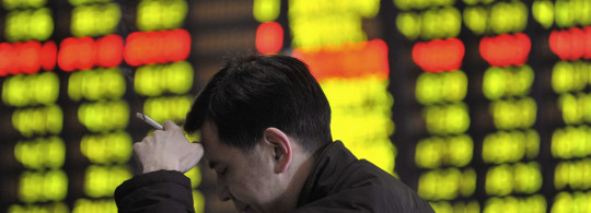 A man smokes in front an electronic board showing stock information at a brokerage house in Shenyang
