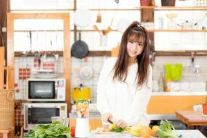 キッチンで野菜を切っている女性