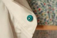 Le bouton de col cousu en patte d'oie