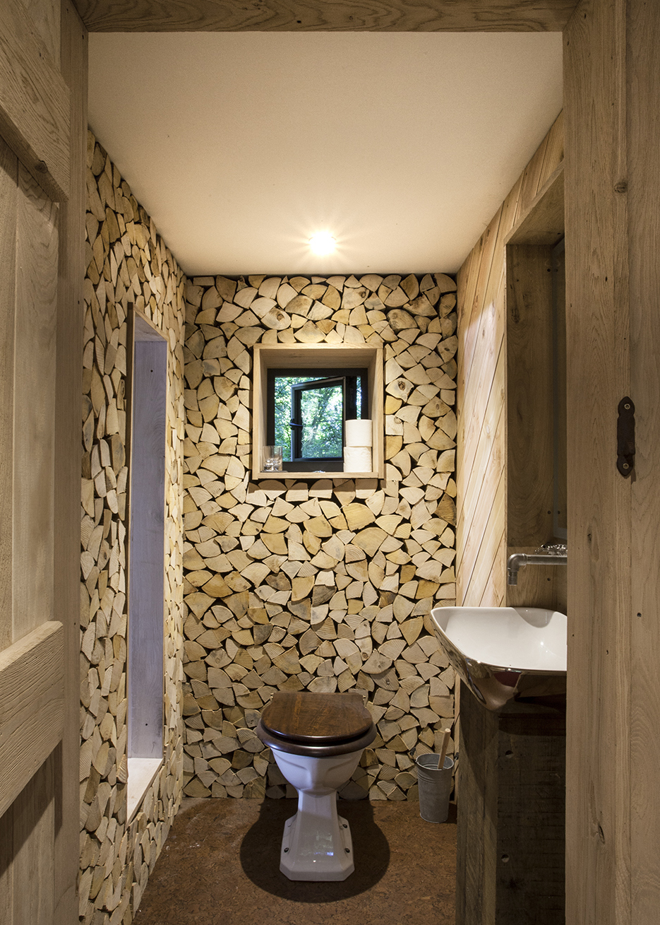 1.7craftycamping-thewoodsmanstreehouse-log-wall-loo