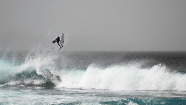 Surfer jumping off a wave