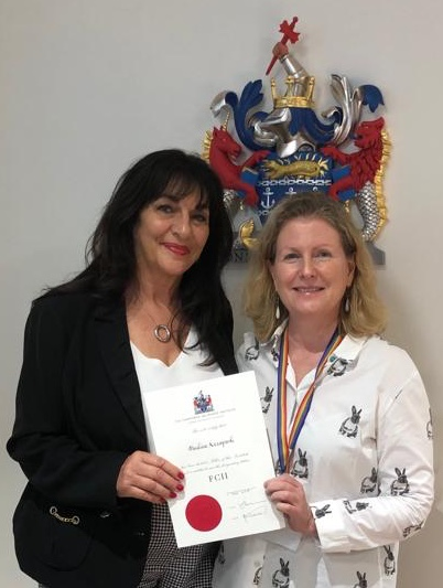 FCII CEO Sian Fisher (on right) presents Pauline Azzopardi (on left) with her Fellowship scroll. (source: press statement)