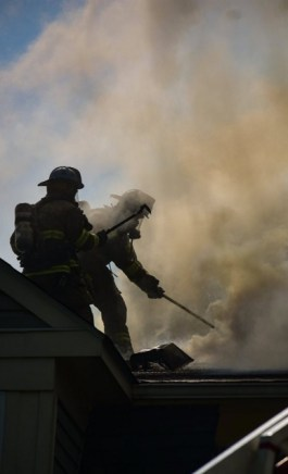 "Part of the roof crew opening up at Warren Way; the ""Raptor"" end of left roofman's Hawk Tool is silhouetted in front of the other firefighter's mask."