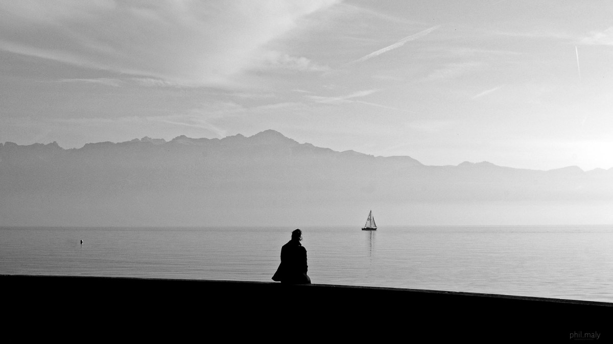 Street portrait of a young girld sitting on a wall near the Lake Leman with a sailing boat