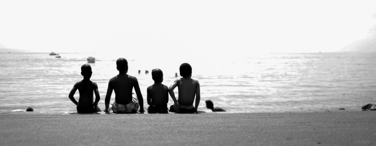 Street shot of 4 young boys sitting in a raw near the lake