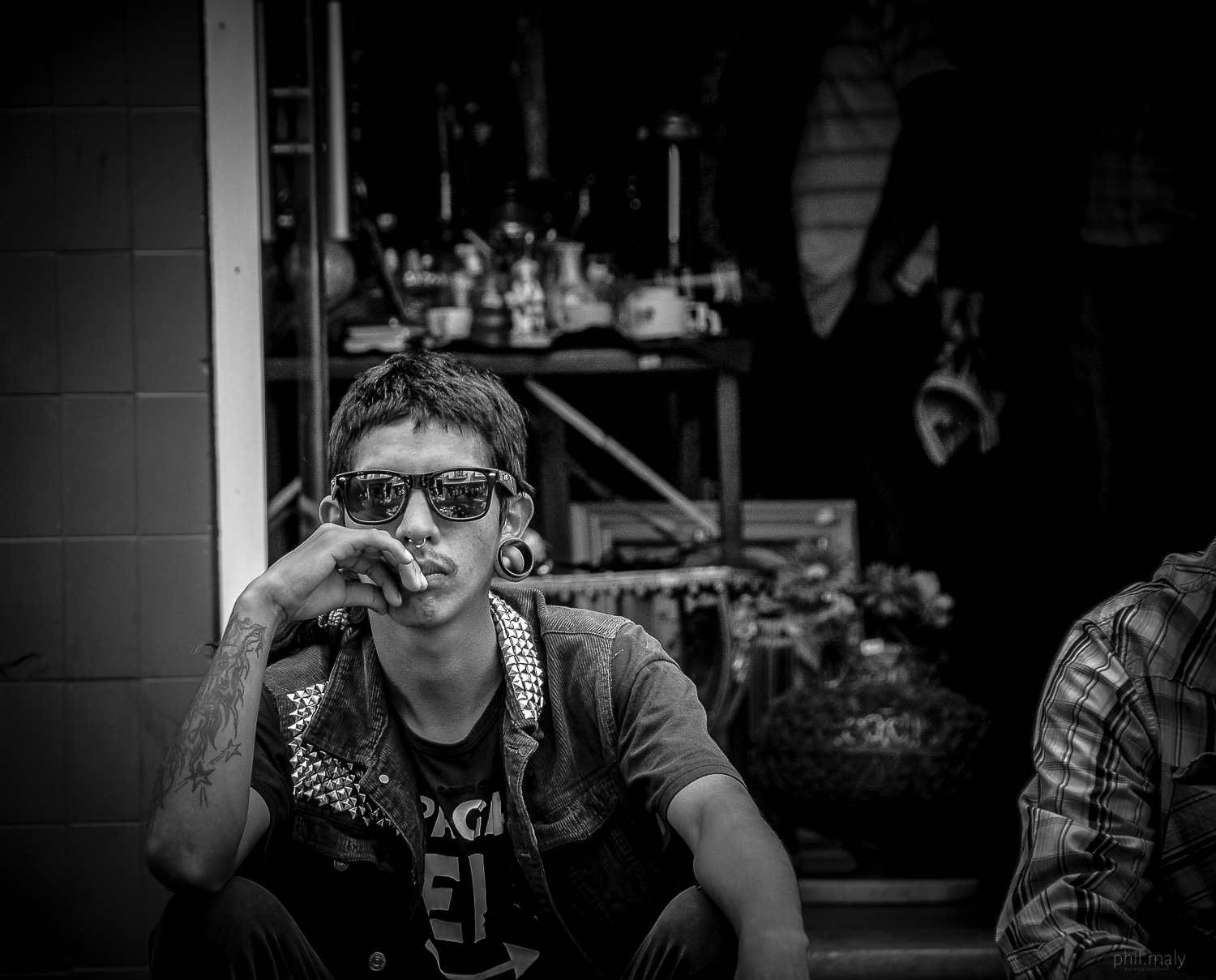 Street portrait of a punk rock young man with dark sunglasses and piercings