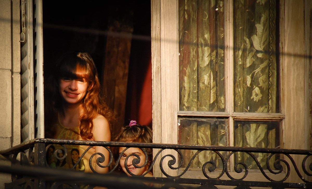Stolen pic of 2 smiling girls at a window in Buenos Aires