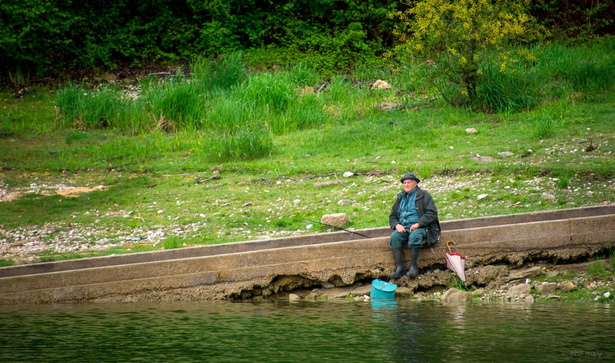 Portrait of an old man fishing near a lake