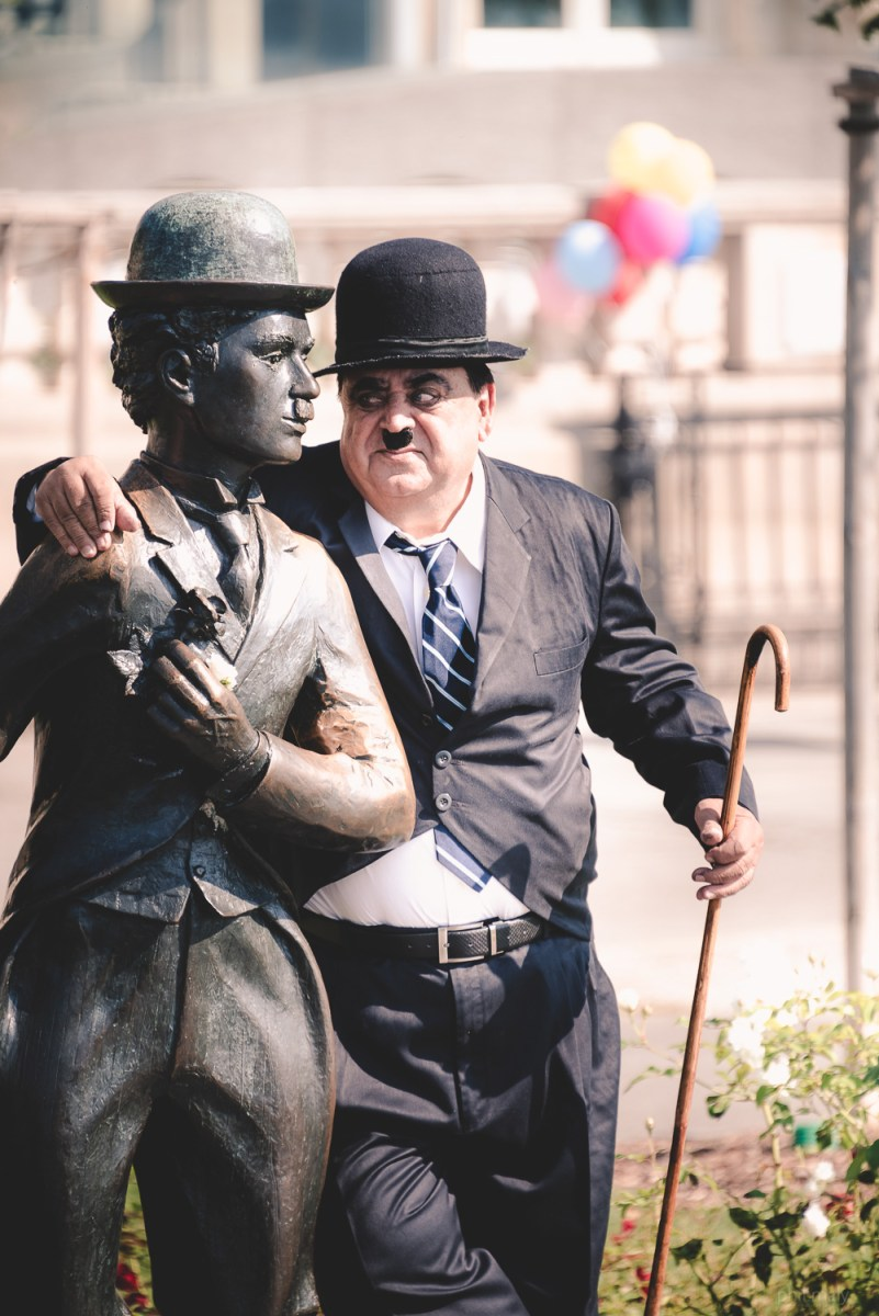 Street portrait of a man dressed up like Charly Chaplin next to his statue