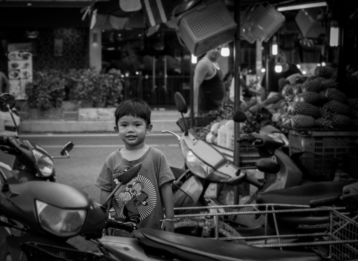 Street portrait of a little young boy smiling at the camera