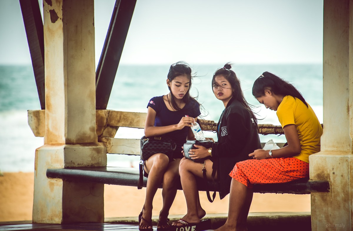 Three thai girls chatting together on the beach of Karon
