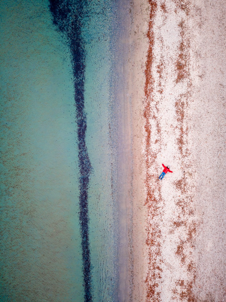 Top down drone shot of a boy with a red jacket on the beach of the lake Leman