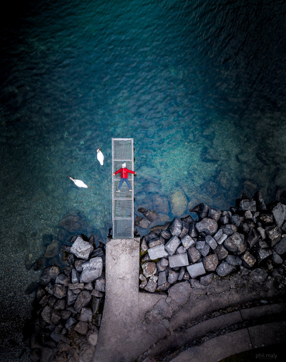 Top down drone shot of a boy with a red jacket laying on a small pier with 2 swans