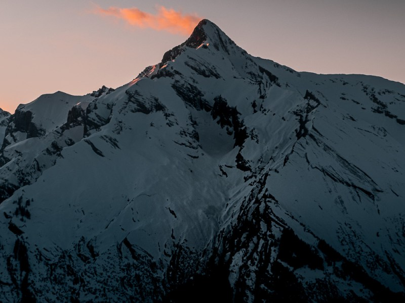Single pink cloud merging with the summit of the Haut-de-Cry