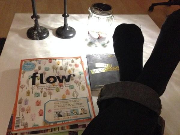 Sonnenglas mit Kastanien und Muscheln drin, Zeitschrift-Ensemble und entspannten Füßen