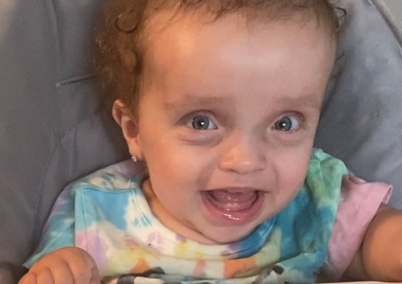 hailey smiling in high chair