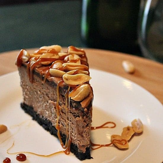 Triple Chocolate Cheesecake with Caramel Sauce and Salted Peanuts. Oreo crumb base, creamy chocolate cheesecake, perfect ganache, smothered in a delicious caramel sauce and salted peanuts.