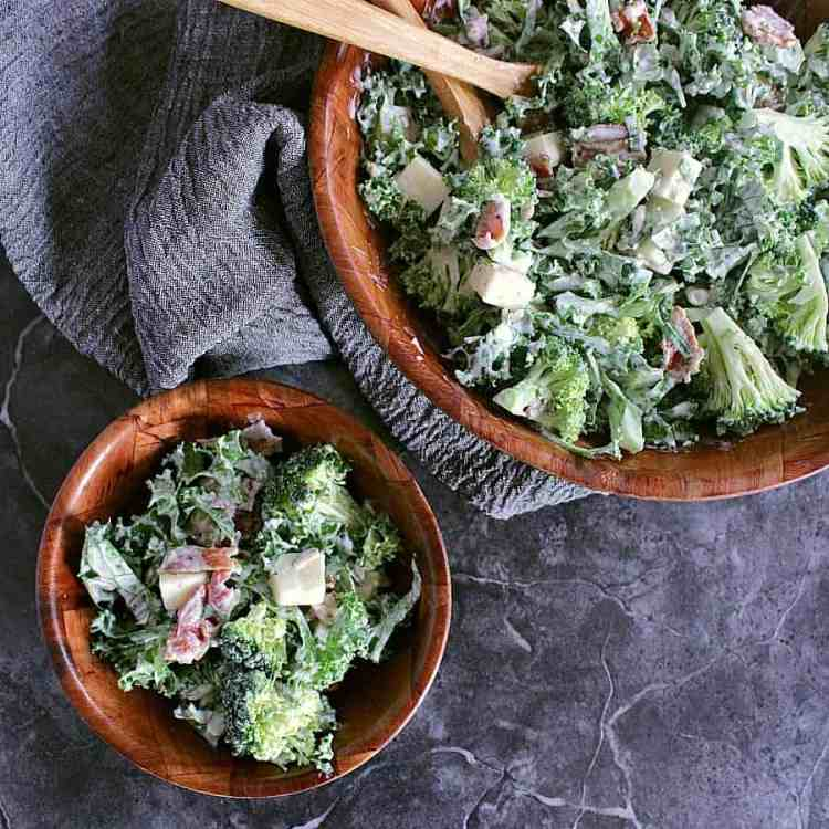 Serving bowl with low carb broccoli salad with serving spoons. Side salad beside it.