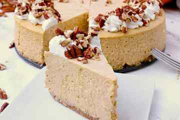 One slice of Keto Pumpkin Cheesecake in front of the remaining cheesecake, garnished with whipped cream and pecans.