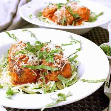 Low Carb Spaghetti and Meatballs with Zoodles. Garnished with freshly grated parmesan and basil.
