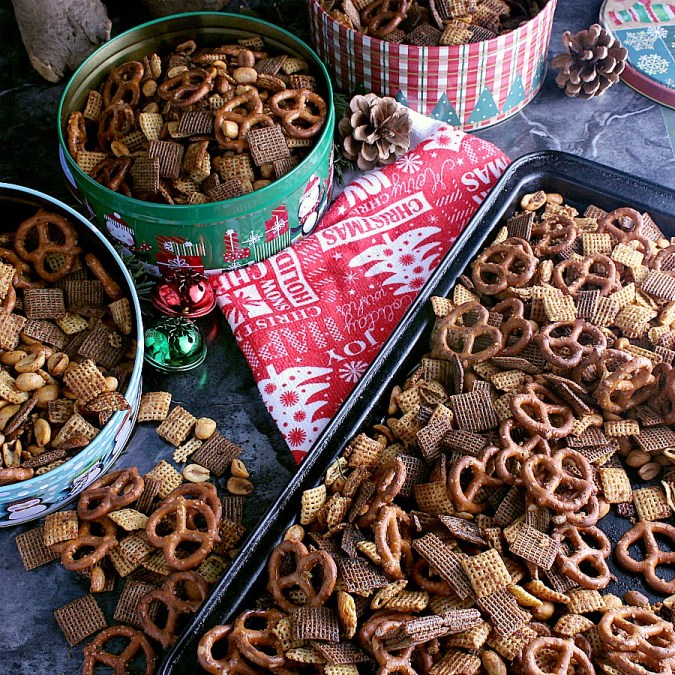 Baking tray and three separate Christmas tins filled with Addicting Christmas Chex Mix.