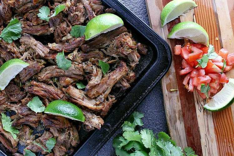 Freshly baked pork carnitas on a baking sheet with fresh limes and diced tomatoes