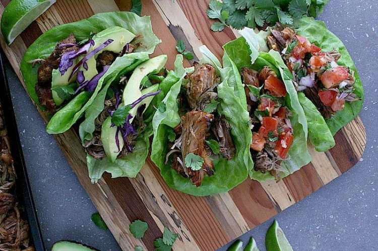 Instant Pot Carnitas loaded into butter lettuce wraps with avocado and cabbage or pico de gallo.