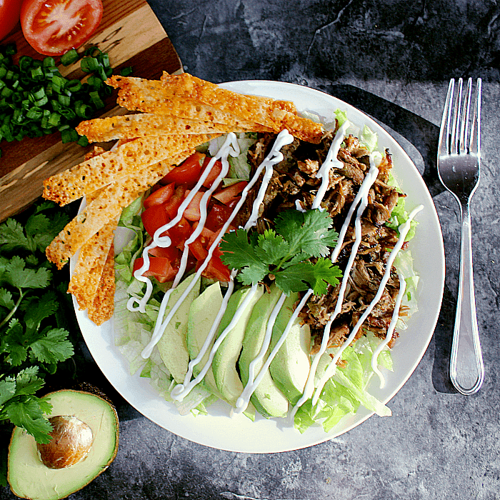 Salad loaded with leftover carnitas, avocado, tomato and cheese crisps.