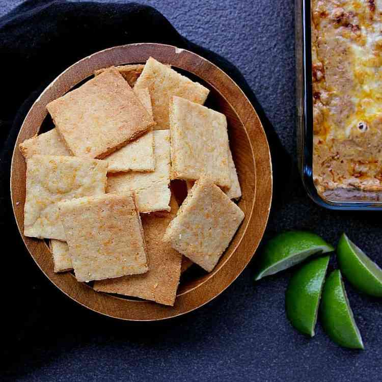 Bowl of low carb cheese crackers, next to a baking dish of hot bean and cheese dip.