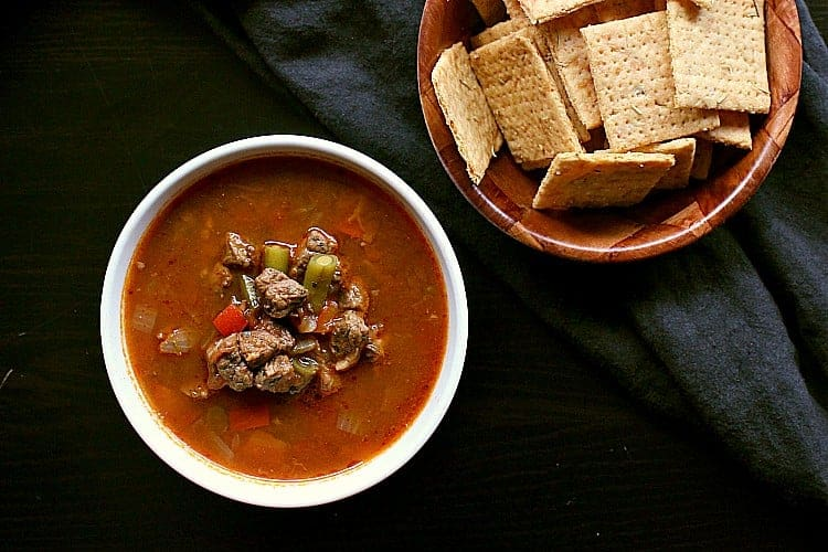 A bowl of vegetable beef soup next to a bowl of low carb crackers.