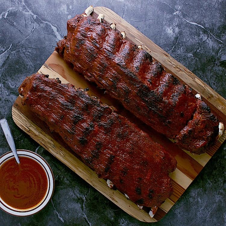 Two racks of ribs, coated in barbecue sauce.