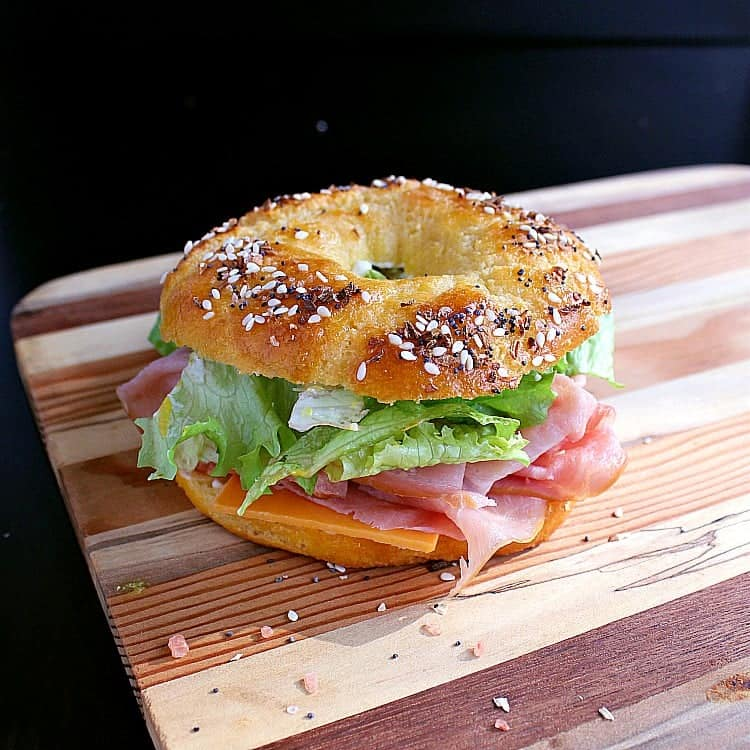 Bagel sandwich with mayonnaise, mustard, cheddar cheese, ham and lettuce.