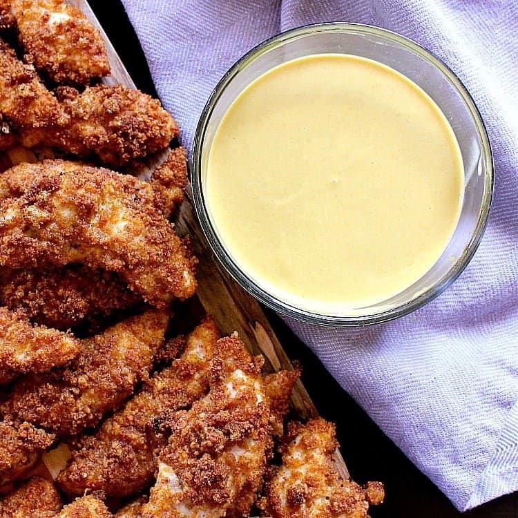 Keto Honey Mustard next to a platter of crispy chicken tenders.