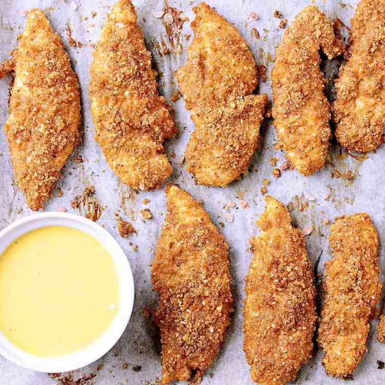 Baking sheet filled with Crunchy Low Carb Baked Chicken Tenders hot from the oven, filling the air with their delicious aroma.