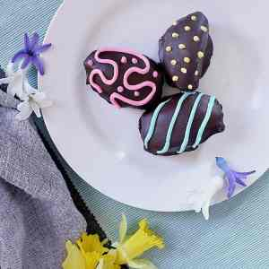 Three decorated Low Carb Easter Eggs on a plate, surrounded by spring flowers.