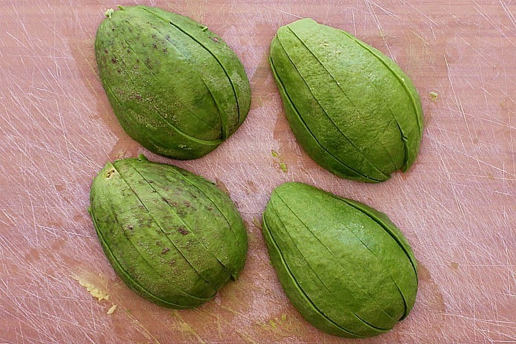 Four avocado halves, laying on a cutting board, each sliced into 6 wedges.