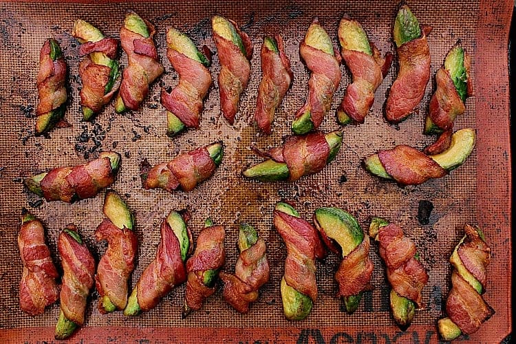 Bacon wrapped avocado fries, fresh from the oven, still resting on the baking sheet before being transferred to paper towel.