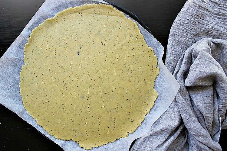 Fathead pizza dough on a pizza pan, pricked all over with a fork, ready for the oven.