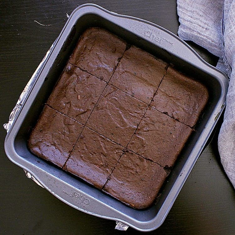 8x8 baking dish filled with the baked brownie which is cut into 9 squares.