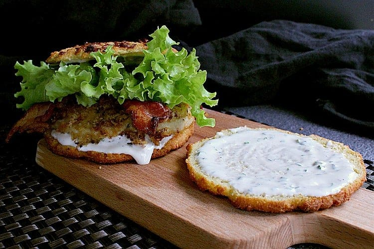 Bottom bun covered with ranch dressing. A fully built Low Carb Bacon Ranch Chicken Burger in the background.