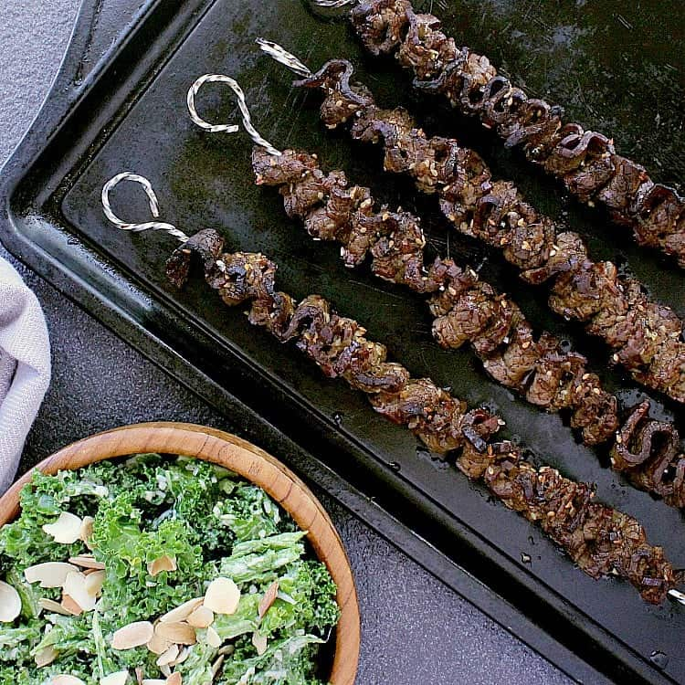 Baking sheet with 4 keto teriyaki beef skewers, fresh from the oven. A bowl of kale caesar salad next to it.