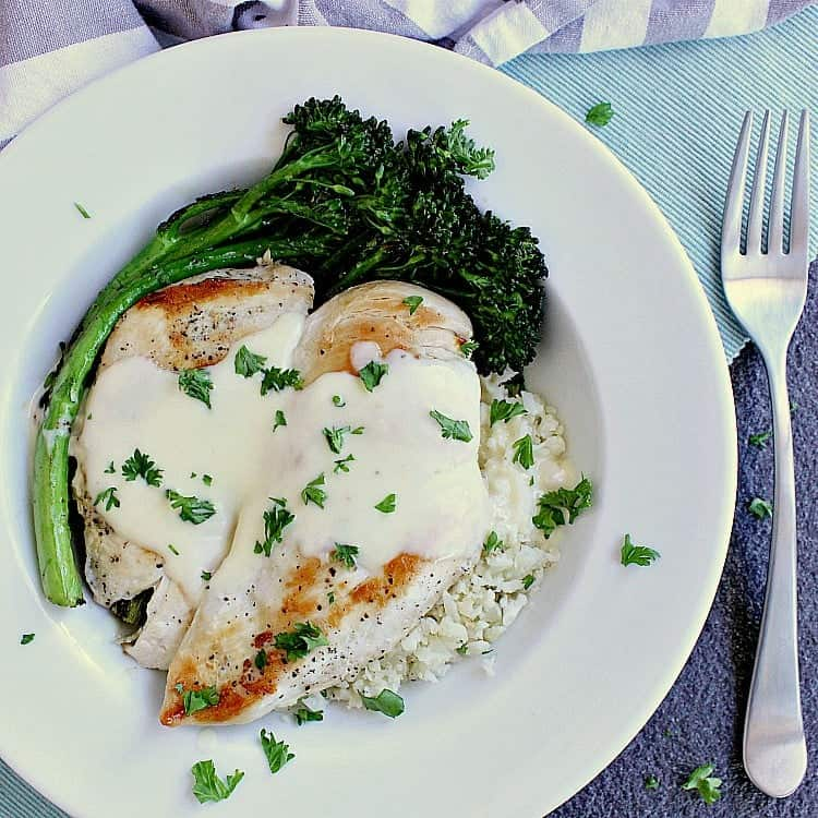 Plate with cauliflower rice, chicken breast, keto alfredo sauce and fried broccolini.