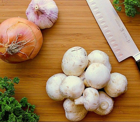 Cutting board with mushrooms, onion and garlic.